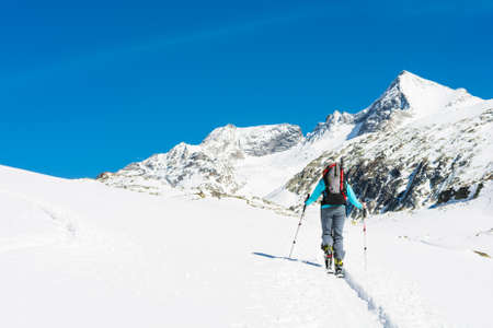touring: Ski touring in sunny weather. Female skier ascending a trail.