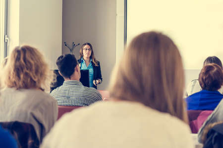speach: Business woman delivering a speach. Audience at a conference. Stock Photo