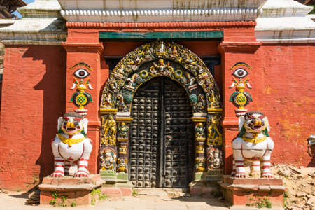 Temple gate guarded by deities. Budist monastery at Durbar square in Kathmandu.