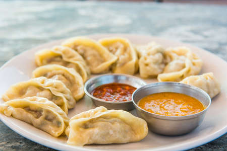 Plate of traditional momos. Steam cooked momos with sauce.