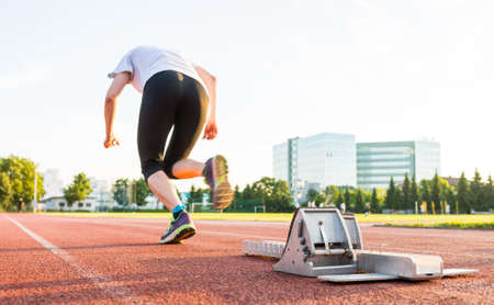 starting block: Side view of sprinter launching from a starting block.