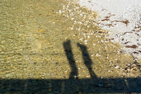 facing each other: Shadow silhouette of a couple facing each other. Couple standing on a bridge.