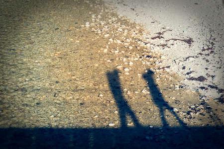people shadow: Couple walking on a bridge crossing a river.