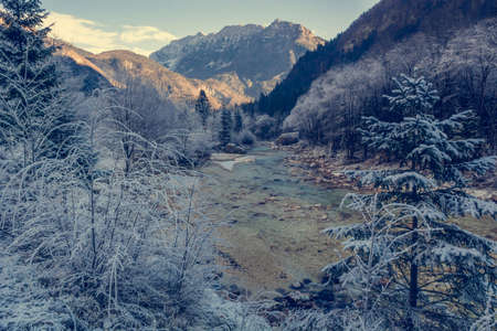 dawns: Mountain river in river. Surroundings covered with frost and ice. Stock Photo