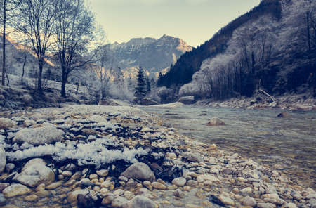 dawns: Frozen river bank. Closeup of mountain river with frst covering stones. Stock Photo
