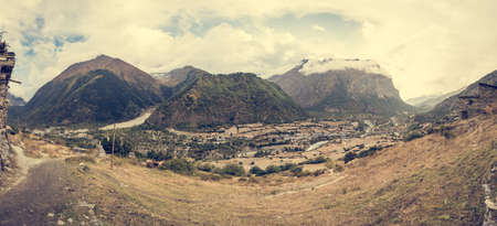 clody sky: Mountain panorama with traditional stone build village. Annapurna circuit in Nepal.