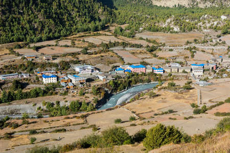 nepali: Traditional river village. Nepali village situated at river bank.
