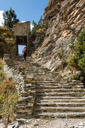 ascending: Trekker ascending stone steps. Annapurna circuit in Nepal.