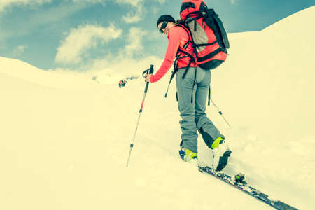 back country: Attractive young skier looking over her shoulder. Back country skiing.