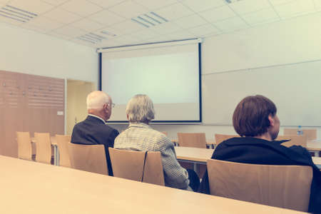 faculty: Audience at thesis presentation in a classroom. Concept of education and success.