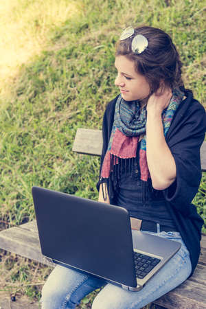 working stiff: Young woman rubbing her neck while working on a laptop. Millenial working in a park. Stock Photo