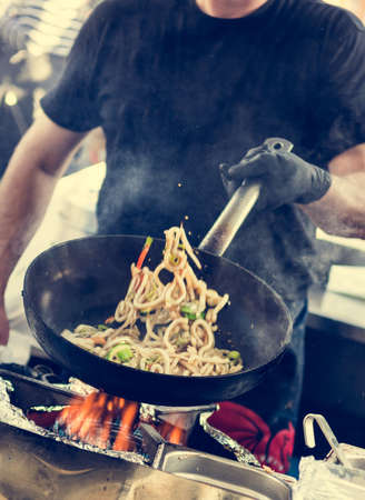 street market: Chef making tasty noodles in a wok. Street food concept. Stock Photo