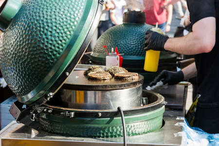 food photography: Chef preparing tasty burgers at outdoor stand. Street food photography. Stock Photo