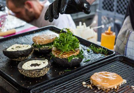 Chef preparando sabrosas hamburguesas en el stand al aire libre. Fotografía de comida callejera. Foto de archivo - 59426654