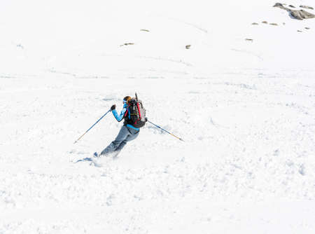 adrenaline rush: Female skier tackling a steep slope. Ski touring in the mountains.