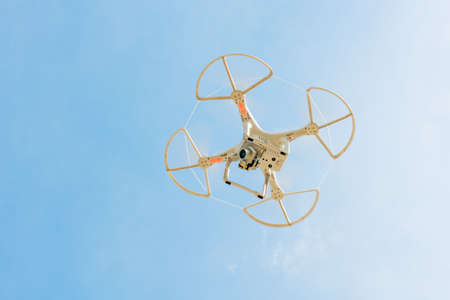 under surveillance: Drone flying in the sky. Hovering quadcopter- view from bellow.