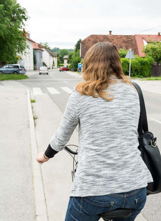 casually dressed: Casually dressed woman cycling. Healing is a healthy way of transportation. Stock Photo
