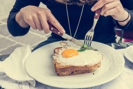 Attractive woman enjoying sunny side up egg on french toast. Breakfast in the city. Banco de Imagens