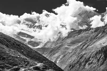 engulfed: Snow covered mountain top engulfed in clouds. Annapurna region in Himalaya.
