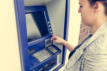 withdrawing: Attractive brunette withdrawing money. Entering pin number.