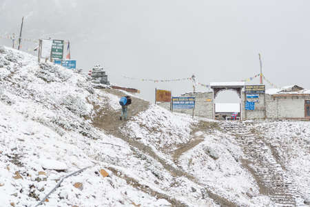 sherpa: Thorong La, Nepal - October 15: Sherpa delivering supplies to high altitude base camp at 4540 m in snow blizzard, on October 2015 in Thorong La, Nepal.