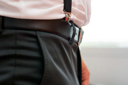 suspenders: Closeup of belt with suspenders. Groom ready for ceremony. Stock Photo
