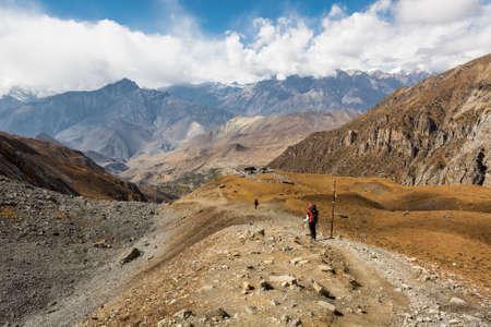 Trekker descending mountain on dirt path surrounded by wasteland. Muktinath region along Annapurna circuit trek in Nepal. Stock Photo