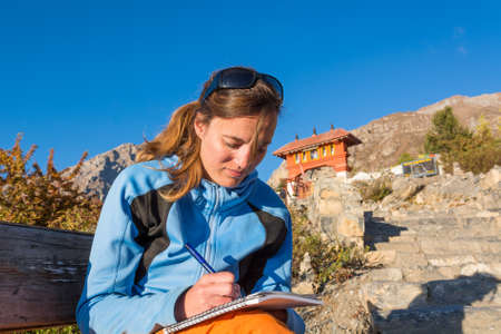 Attractive brunette writting a travel diary. Exploring new countries.