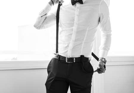 suspenders: Groom pulling on the suspenders. Final wedding preaprations.