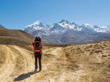 Lonely trekker on a crossroad of two roads towards mountains. Stock Photo