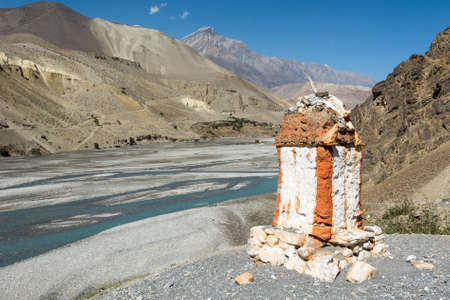 Border stone at the river bank. Stock Photo