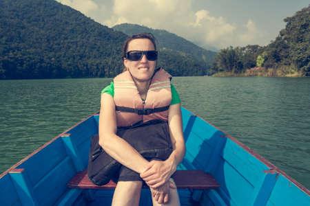 phewa: Happy tourist enjoying boat ride.