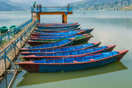phewa: Colorful boats anchored to pier. Stock Photo
