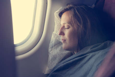Female passenger sleeping covered with blanket. Stock Photo