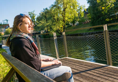 Young and attractive woman meditating with closed laptop.