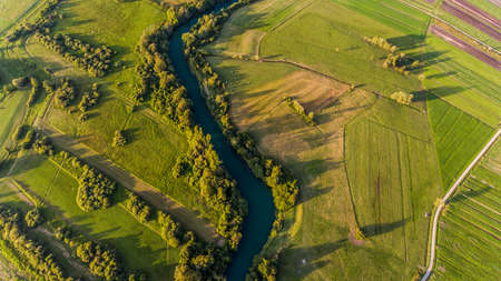 River bend surrounded by fields from birds eye view.