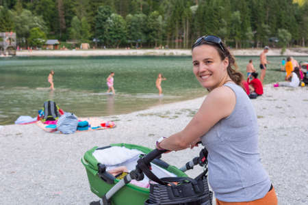 brunete: Happy mother pushing a baby stroller. Stock Photo