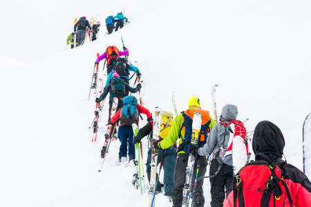 skiers: Group of cross-country skiers ascending a steep slope.