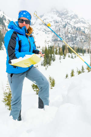 Female rescuer searching for avalanche victim.