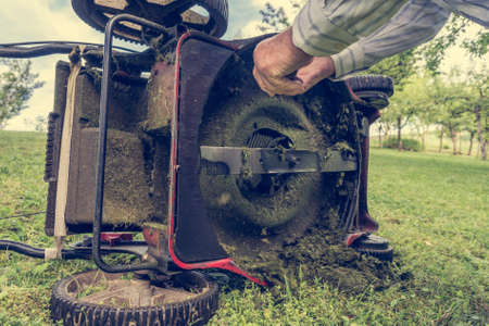 Man cleaning lawn mower blade. Stock Photo