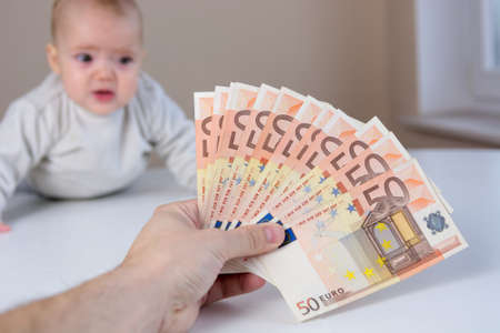 Crying baby looking at a pile of money.