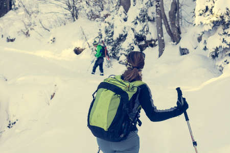 Female hiker looking across her should in winter forest.