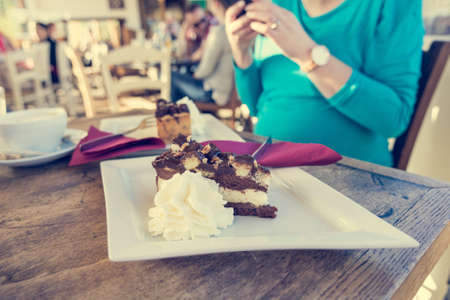 Pregnant woman taking a snapshot of delicious cake.