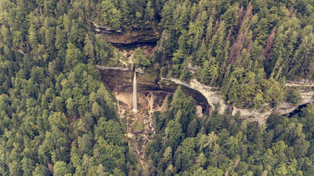 Aerial view of double water fall in a forest.