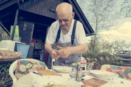 Elderly man setting a table outside. Standard-Bild