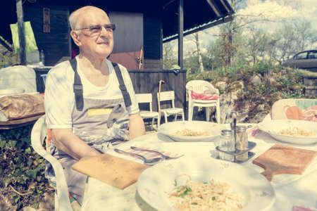 Elderly man sitting at lunch table outdoor.