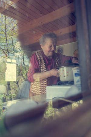 Elderly woman cooking.
