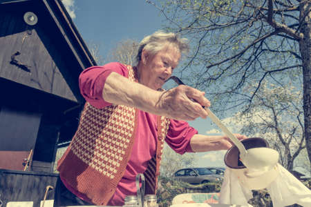 Elderly woman serving a lunch outdoor.