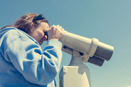 Woman looking through coin operated binoculars at seaside. Stock Photo