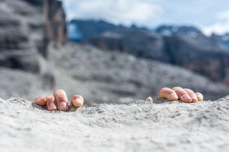 Closeup of fingers gripping a rock.